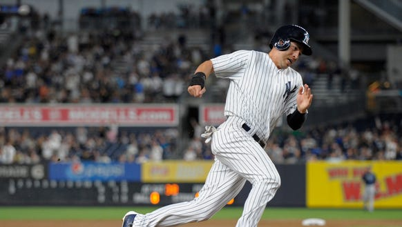 New York Yankees' Rob Refsnyder rounds third base attempting