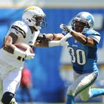 San Diego Chargers wide receiver Keenan Allen (13) stiff arms Detroit Lions defensive back Josh Wilson (30) after a reception in the first half at Qualcomm Stadium.