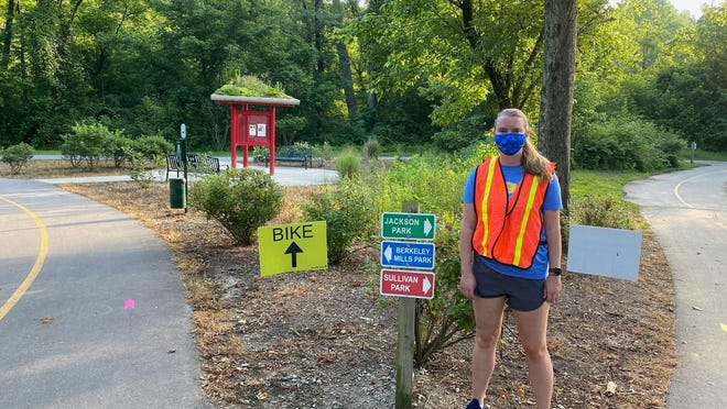 A volunteer stands by on the Oklawaha Greenway during the relocated Asheville Triathlon held July 19.
