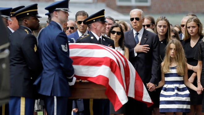 Joe Biden, accompanied by his family, holds his hand over his heart as he watches an honor guard carry a casket containing the remains of his son, former Delaware Attorney General Beau Biden, into St. Anthony of Padua Roman Catholic Church in Wilmington, Del.