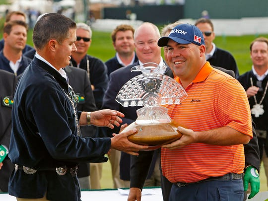 Kevin Stadler receives the trophy after winning the Waste Management Phoenix Open on Feb. 2, 2014 at TPC Scottsdale.