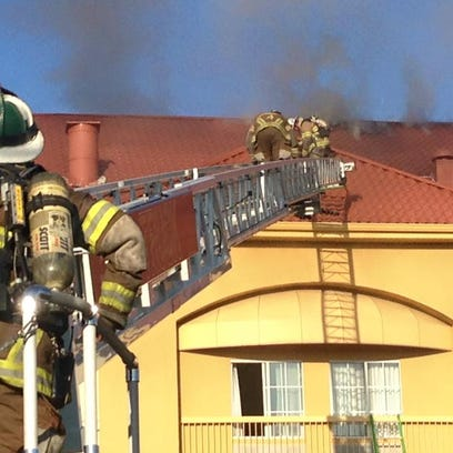 Firefighters work on the roof of the La Quinta Inn,