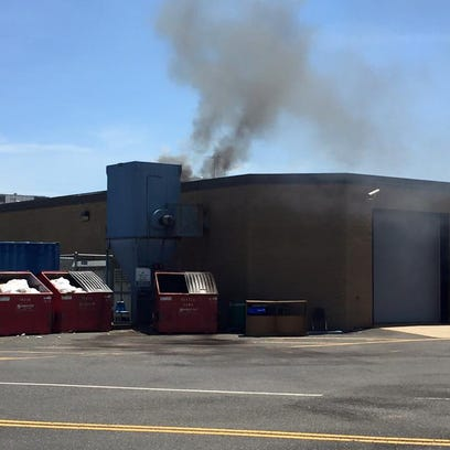 Smoke is seen drifting from the roof of Holmdel High