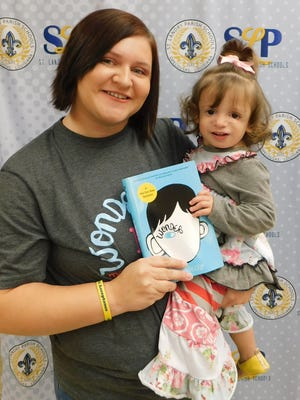 """Candice Robin and daughter, Anna Lise, donated copies of the book """"Wonder"""" to officials at the St. Landry Parish School Board on Monday to help create awareness for Treacher Collins syndrome, a genetic disorder, which affects facial appearances and causes difficulty with hearing and speech. Robin purchased 200 copes of the book through her personal fund raising. The books will be used by students in the school district."""