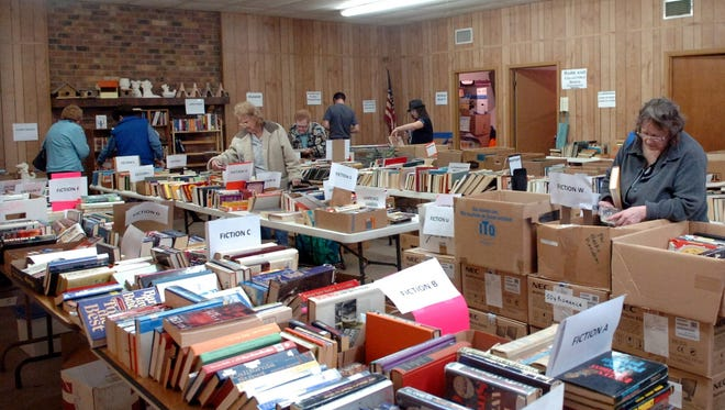 Customers look through the fiction section of the Friends of the Library used book sale. This month's sale will be April 8 at the downtown warehouse.