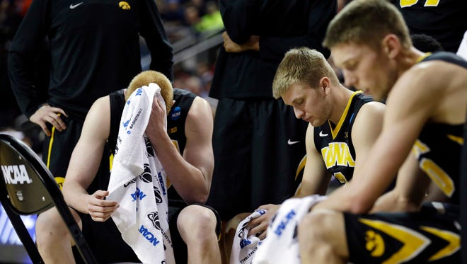 Iowa's Aaron White, left, and teammates rest during a timeout against Gonzaga in the second half of an NCAA tournament college basketball game in the Round of 32 in Seattle. In the NCAA tournament, more frequent stoppages in play-- leave coaches and players with time on their hands.