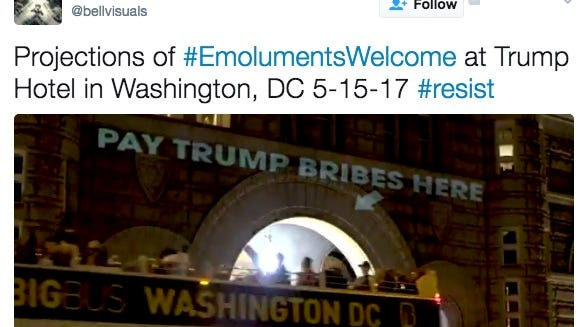 """An artist projection the words """"Pay Trump bribes here"""" on the Trump International Hotel in Washington on Monday night."""