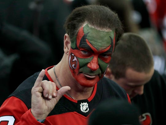 "Patrick Warburton, the actor who played David Puddy on ""Seinfeld"" and wore makeup supporting the New Jersey Devils during an episode of the show, gestures at the end of Game 4 of an NHL first-round hockey playoff series between the Devils and the Tampa Bay Lightning, Wednesday, April 18, 2018, in Newark, N.J. The Lightning won 3-1. (AP Photo/Julio Cortez)"