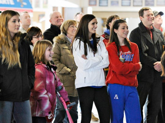 Families, students, fans and players watch a highlight reel of photos and video Tuesday during a sendoff for the Apollo High School hockey team.