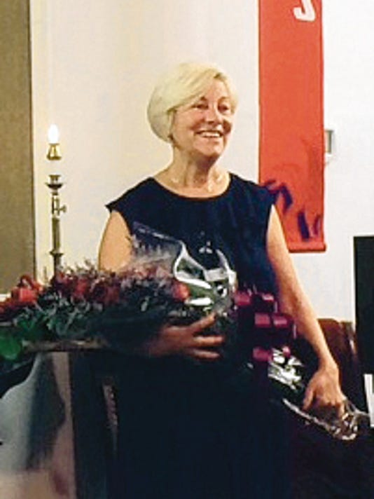 Debbie Gwin receives a bouquet of roses during First Presbyterian Church Organist Appreciation Day, which the church held in her honor on July 5.