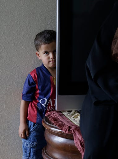 Mohannad Almasri, 2, the youngest of the four children, is shy and slow to warm up to strangers. He hides behind the TV in his living room where his mother, Rasha, is sitting March 5.