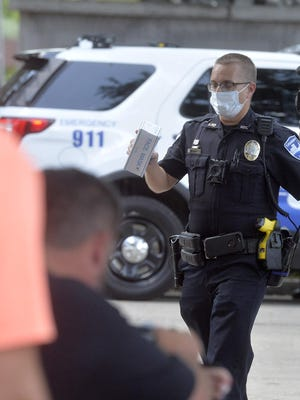 FILE PHOTO: Cpl. William Barnett hands out face masks to those needing one in City Market.