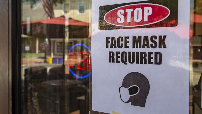 A reminder to patrons, a Face Mask Required sign is posted on the front window at a business.