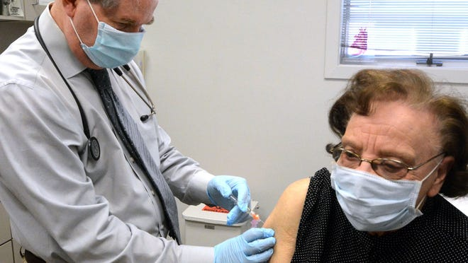 Dr. Paul Deutsch gives Lorraine Hebert, 87, of Jewett City a flu shot Wednesday at his office in Norwich.