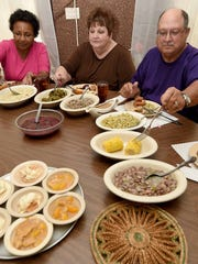 At a table full of diners from Louisiana, (from left) Loraine Oubre of Vacherie, La., and Lois and Roscoe Besson of Grand Isle, La., serve themselves at The Dinner Bell in McComb.