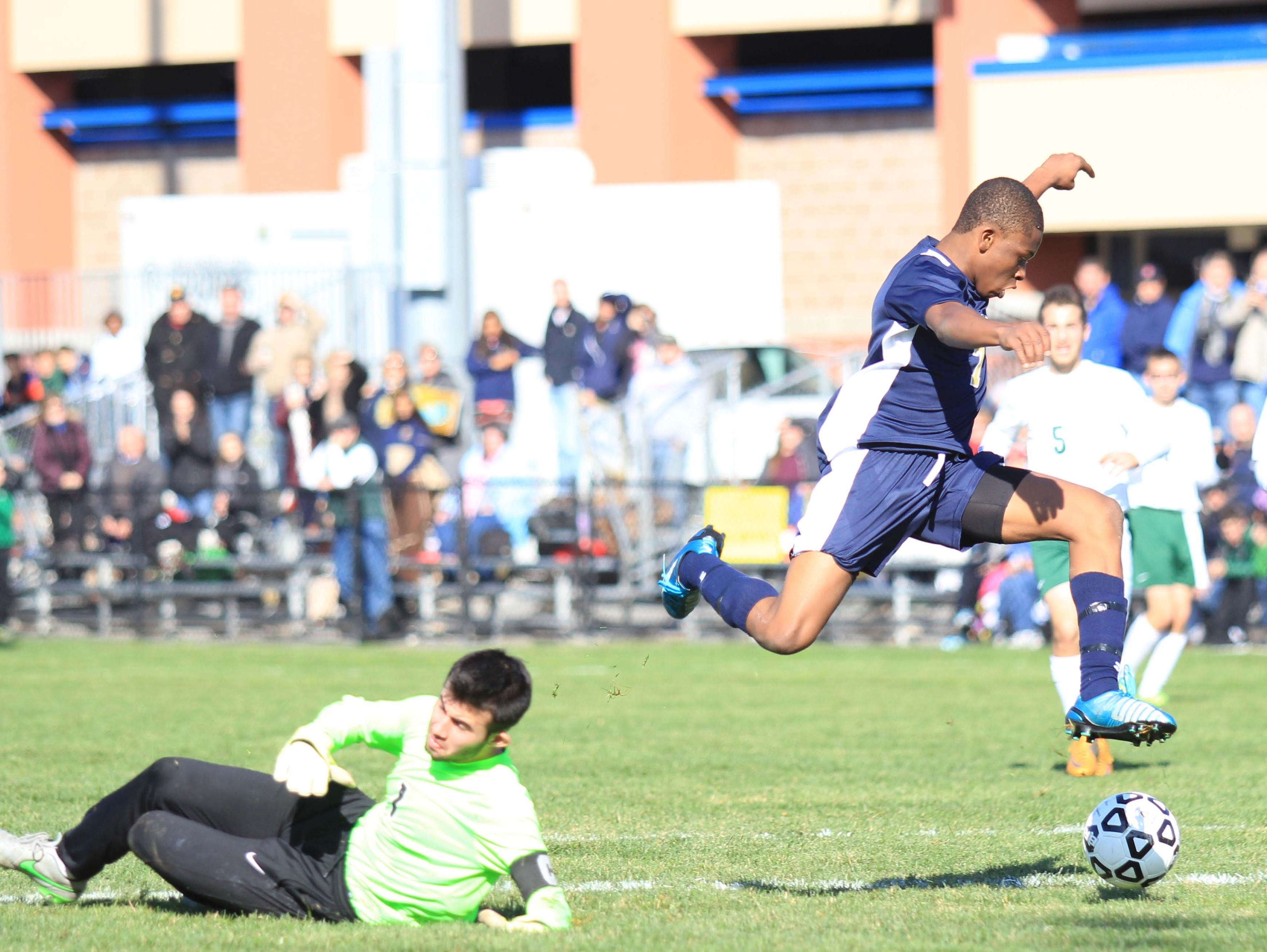Notre Dame's Rocco Coulibaly (right) leaps over goalie Noah Dunn to score during the NYSPHSAA Class C final in Middletown.