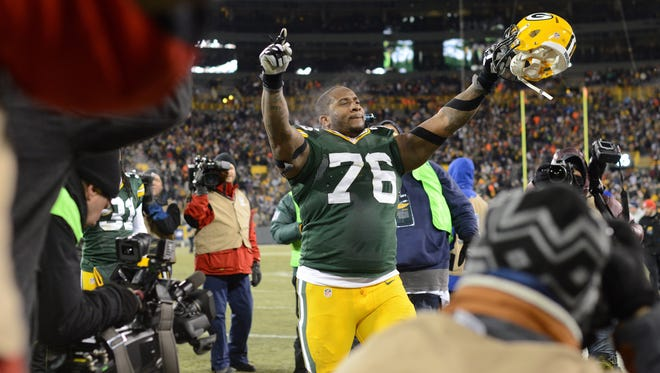 Green Bay Packers defensive tackle Mike Daniels (76) raises his hands to the crowd as he makes his way to the locker room following team's victory over the New England Patriots.