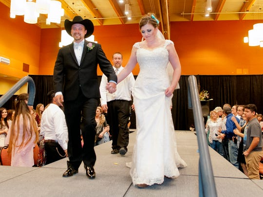 Mr. and Mrs. Garrett Arnold leave the runway of the Las Cruces Bridal Showcase Sunday afternoon after the couple were married moments earlier.
