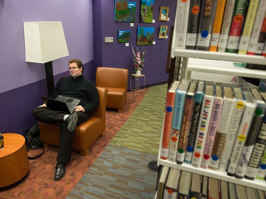 Jake Kowalski at the Dover Public Library on Friday Nov. 14, 2014, studying for his certified public accountants test while his wife Tamora Kowalski is at her job at the Biggs Museum of American Art.