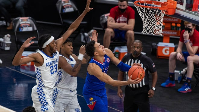 Kansas forward Jalen Wilson, right, attempts a layup past Kentucky forward Isaiah Jackson (23) in the second half of Tuesday night's game at Bankers Life Fieldhouse in Indianapolis. Wilson finished with 23 points and 10 rebounds in the No. 7-ranked Jayhawks' 65-62 victory over the No. 20 Wildcats.