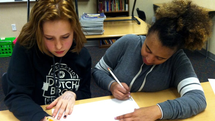 """Lena Morgan-Holt, 14, and Christine Martin, 15, draw a """"treasure map"""" of images to represent their personalities and goals at a Strengthening Families workshop on Jan. 12 at Poulsbo Middle School. The program is hosted by WSU Kitsap County Extension to improve communication between young people 10-14 and their parents."""