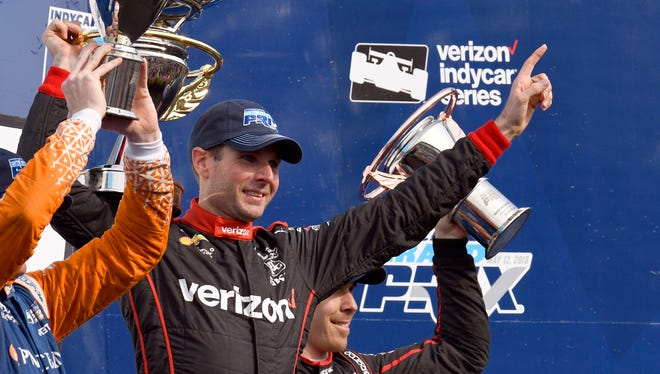 Team Penske IndyCar driver Will Power (12) celebrates on the victory podium after winning the running of the 2018 IndyCar Grand Prix, Saturday, May 12, 2018