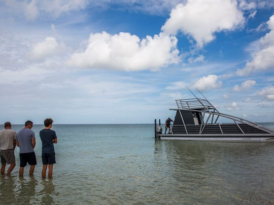 From left, Mike Ballard, Barry Connor, and Jacob Connor, 15, stand in the water as Craig Gaskins works on the Connor's boat out on the Gulf of Mexico in Naples on Wednesday. June 14, 2017. Connor and his son Jacob built the boat as a project together with the help of Connor's business partner Gaskins and family friend and welder Ballard.