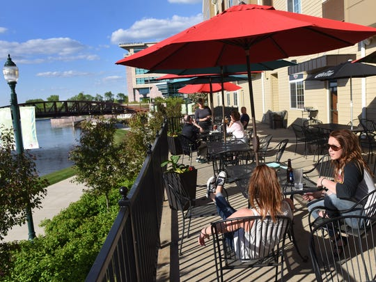 Patrons dine on the patio at Falls Landing Bar and