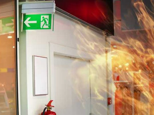 An emergency sign and a fire are seen.