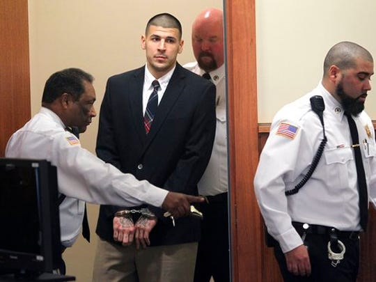 FILE - In this Monday, Dec. 23, 2013, file photo, former New England Patriots NFL football player Aaron Hernandez is led into his court appearance at the Fall River Superior Court in Fall River, Mass. Massachusetts prison officials said Hernandez hanged himself in his cell and was pronounced dead at a hospital early Wednesday, April 19, 2017.