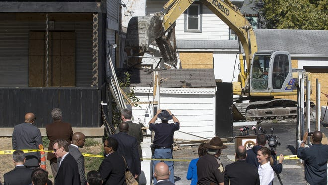 A crane starts the demolition of one of the building of the former Outlaws Motorcycle Club's Indianapolis chapter at  2204 E. New York St. on Tuesday, Oct. 13, 2015. The land housing the compound, which local and federal officials shut down earlier this year after a lengthy investigation into organized crime, will be donated to the city.