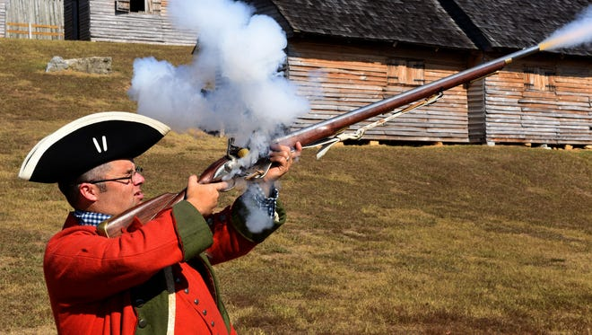Fort Loudoun State Historic Park manager Eric Hughey fires his musket as he teaches a classroom in Colorado via Skype on Tuesday, Nov. 1, 2016. Following his introduction and musket firing, Hughey carries the iPad around the Fort for the students to get a view of the interior of the cabins and grounds.