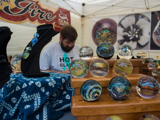 Artist Seth Bickis and his display of art glass.