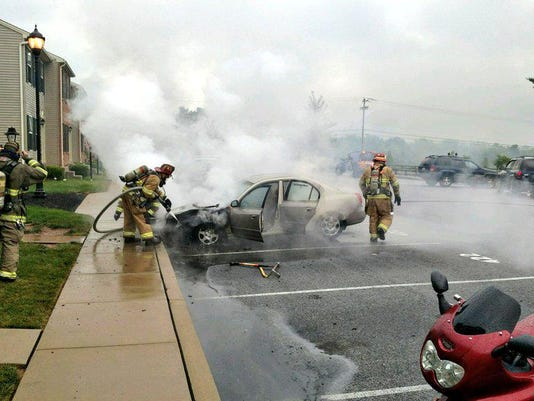 Firefighters work to extinguish a car fire in Conewago Township.