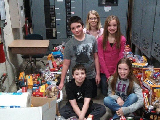 Madison School's food drive resulted in 13 baskets of food and toiletry items to be donated to Madison School families in need. Pictured are sixth-grade leadership students who along with food drive coordinator, Mrs. Peters, prepared the baskets to be delivered before the holiday break.