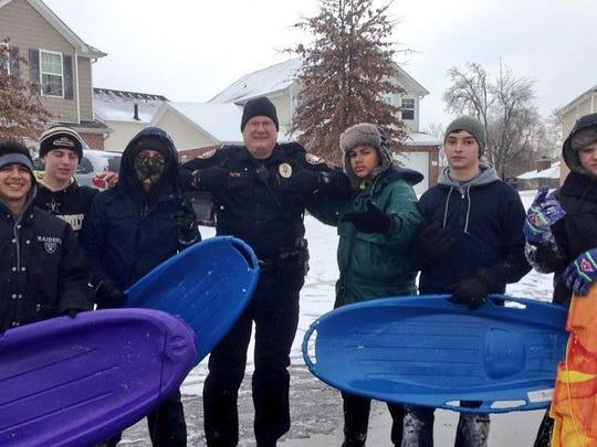 Sgt. Scott Fulton with teenagers sledding in Mt. Juliet's Park Glen neighborhood.