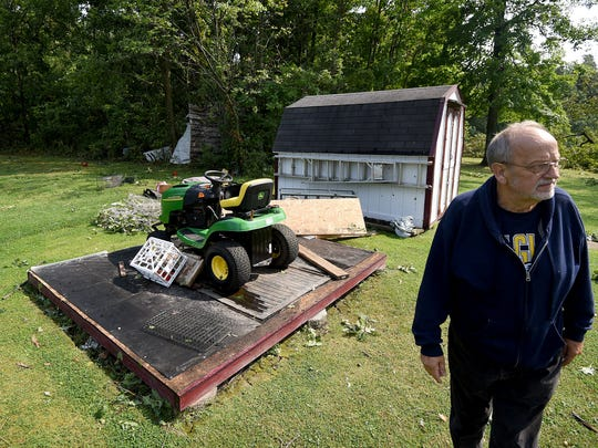Mike Stevens of 2638 Stiving Road surveys the damage to his property after Monday night's storms. The lawnmower behind him was stored in a shed that was picked up by the high winds and tossed into the wooded area behind.