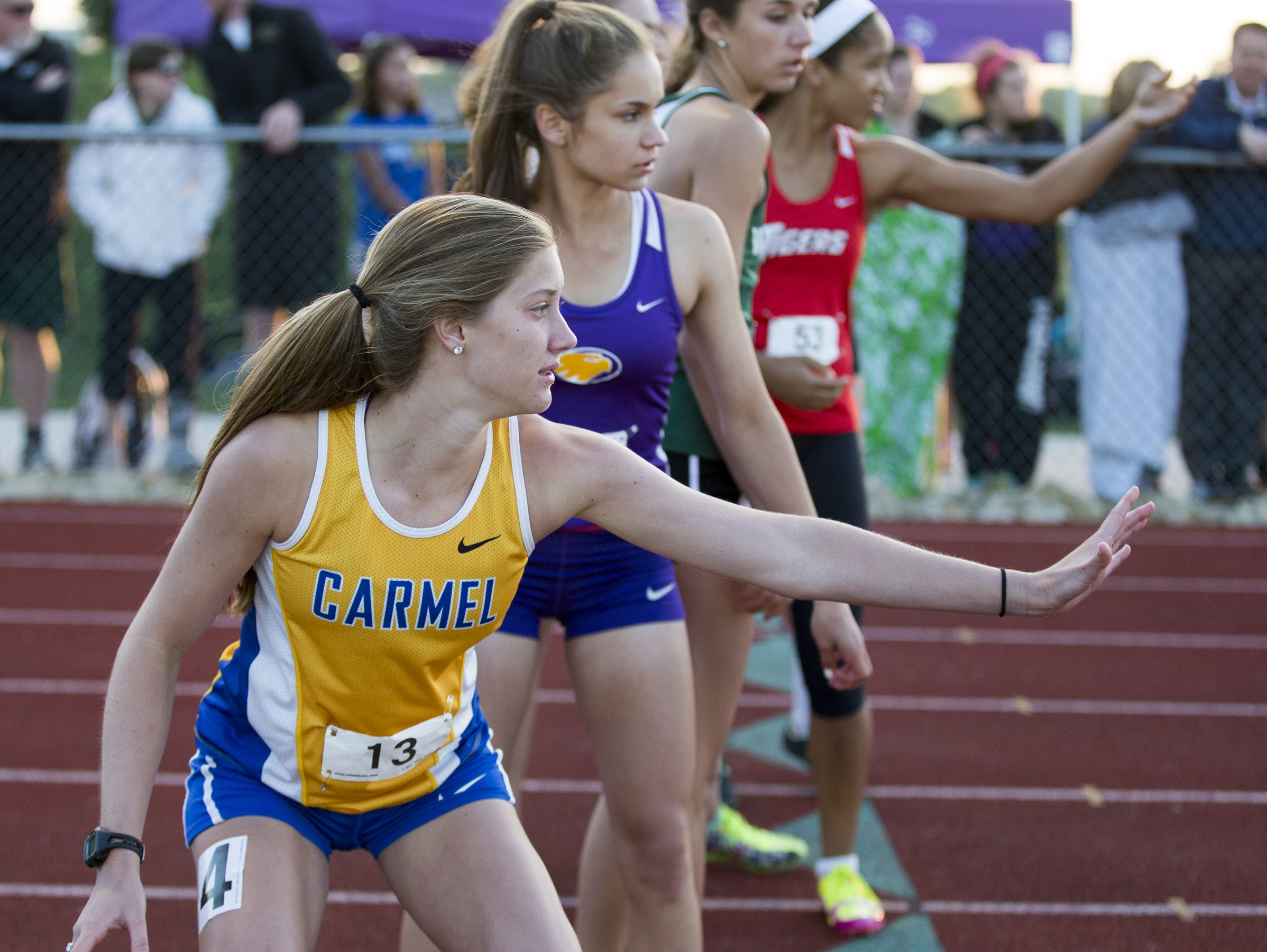 Competitors line up for an exchange, including Haley Harris of winning team Carmel High School, during the 4 X 400 meter race, IHSAA Girls Track and Field Sectional #13, Guerin Catholic High School, Noblesville, Tuesday, May 19, 2015.