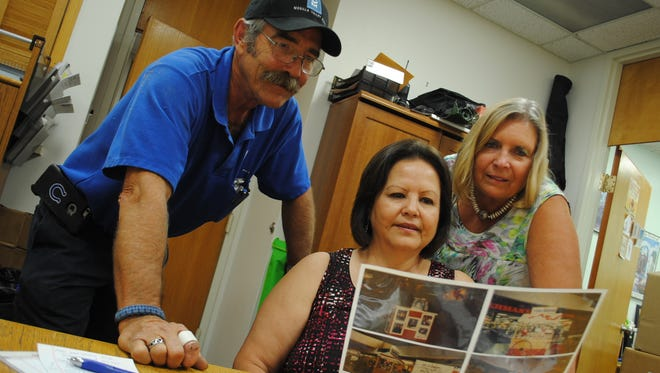Mesilla Valley Mall employees Rick Reichert, left, Marla Hinojos and Susan Palmer reminisce while looking over photos from the mall's history. Reichert and Hinojos were both hired in 1986, five years after the mall's opening.