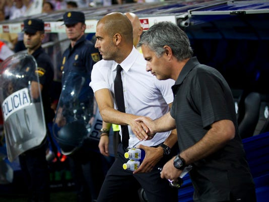 FILE- In this Sunday Aug. 14, 2011 file picture, the then Real Madrid's coach Jose Mourinho from Portugal, right, shakes hands with former Barcelona's coach Josep Guardiola before their Super Cup first leg soccer match at the Santiago Bernabeu stadium, in Madrid. Mourinho and Guardiola will go head-to-head for the first time as English Premier League managers on Sept. 10 when Manchester United and Manchester City meet in the derby at Old Trafford. (AP Photo/Daniel Ochoa de Olza, File)