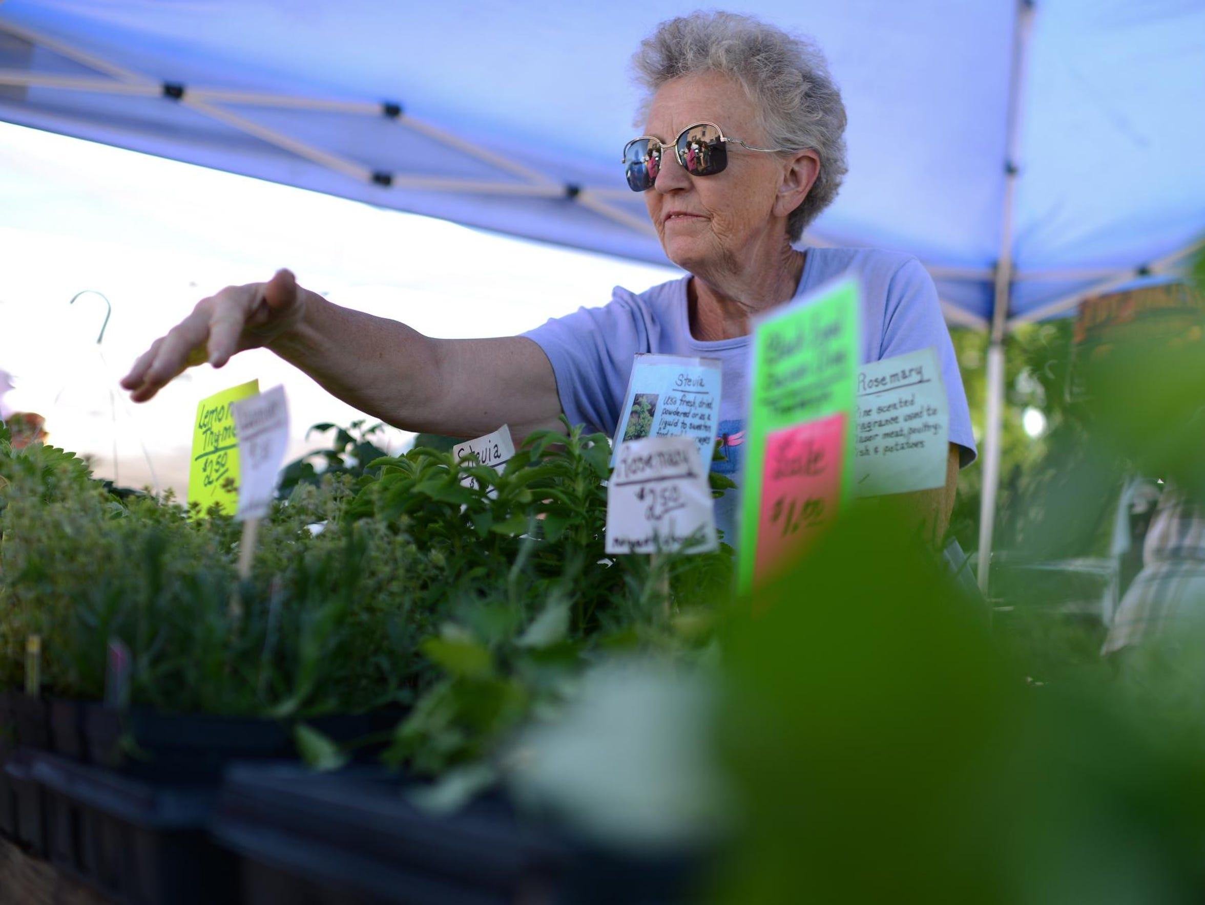 Rita Christman, owner of Christman Gardens, helps a