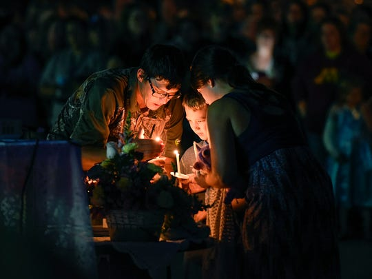 Matt and Kayla Ertl and their son Carter light candles during a candlelight vigil Tuesday in memory of Alayna Ertl, 5, in the parking lot of St. Anthony Catholic Church in Watkins.