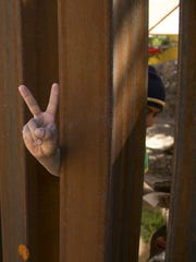 Freddy Perez, 26, flashes a peace sign through the