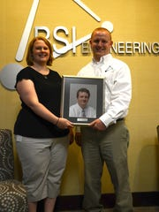 BSI's David Speicher and Kelley Aronson with a portrait of their father, founder Bryan Speicher.