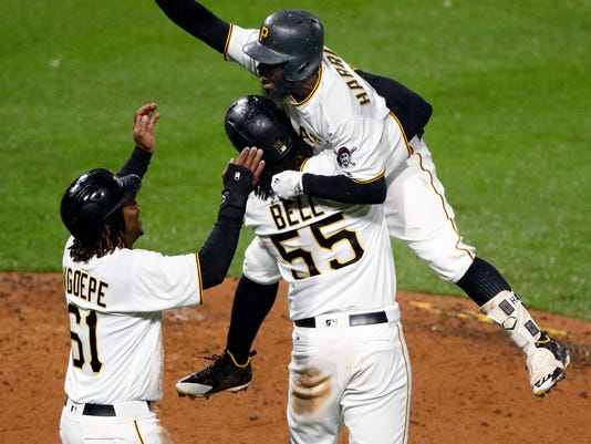 Pittsburgh Pirates' Josh Harrison, top, celebrates with Josh Bell (55) and Gift Ngoepe (61) after driving in Ngoepe with a walk-off single off Milwaukee Brewers relief pitcher Carlos Torres in the tenth inning of a baseball game in Pittsburgh, Saturday, May 6, 2017. The Pirates won 2-1. (AP Photo/Gene J. Puskar)