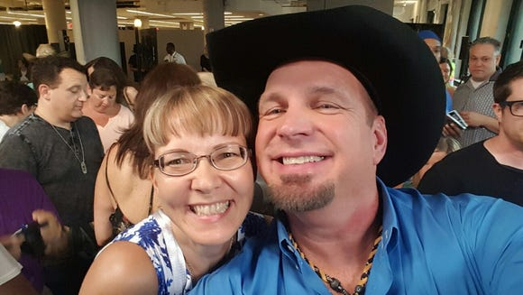 Superfan Tiina Pukki poses with Garth Brooks at a concert