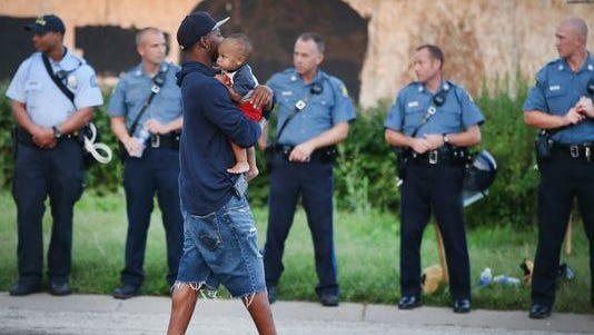 A man carries his child past a row of police officers in Ferguson, Missouri, tasked with keeping the peace at a demonstration to protest the killing of teenager Michael Brown