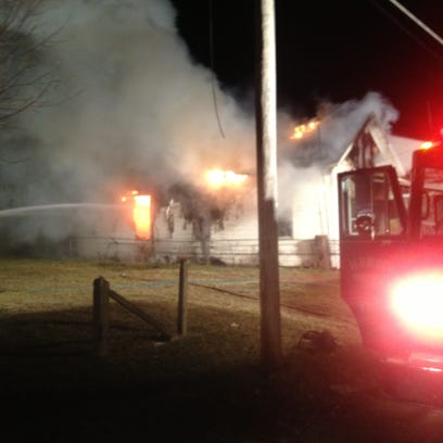Firefighters battle a house blaze at 521 W. Sixth St.