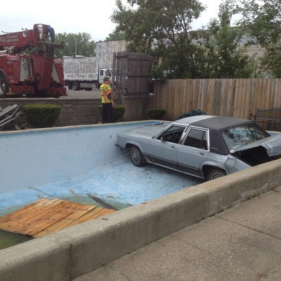 A car ends up in a swimming pool after backing through