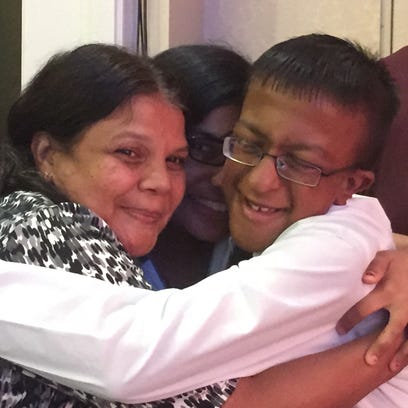 Dev Jaiswal, right, gets a hug from family members